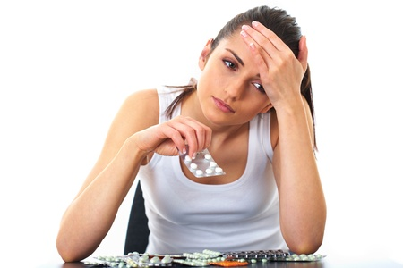 cold woman: stressed attractive young brunette with pile of pills in front of her