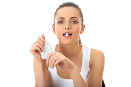 attractive young brunette takes some pills, isolated on white background Stock Photo - 11477480