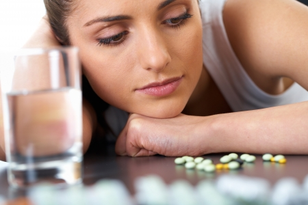 stressed attractive young brunette with some pills and glass of water Stock Photo