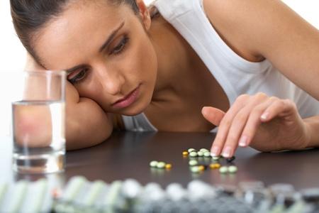 depresi�n: destac� atractiva joven morena con unas pastillas y un vaso de agua Foto de archivo