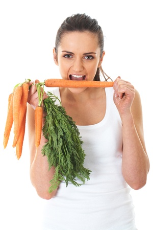 young attractive female holds bunch of carrots and try to eat one of them, isolated on white photo