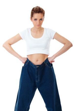 large woman: Attractive young woman shows her old huge jeans, isolated on white