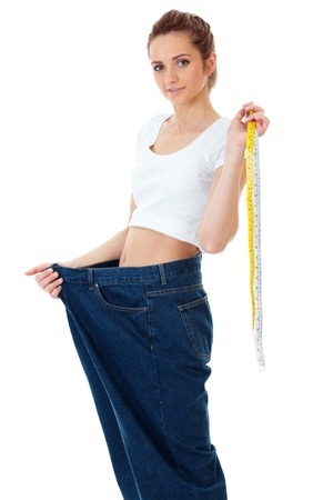 loose skin: Attractive young woman shows her old huge jeans, successful dieting concept shoot over white background