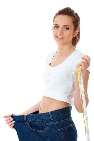 big belly: Attractive young woman shows her old huge jeans, successful dieting concept shoot over white background
