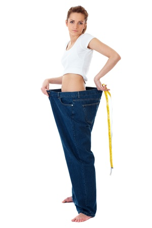 Attractive young woman shows her old huge jeans, successful dieting concept shoot over white background