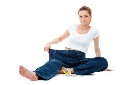 Attractive young woman shows her old huge jeans, successful dieting concept shoot over white background Stock Photo - 11477760