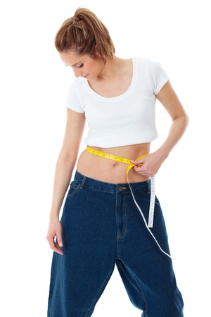 Attractive young woman shows her old huge jeans, successful dieting concept shoot over white background photo