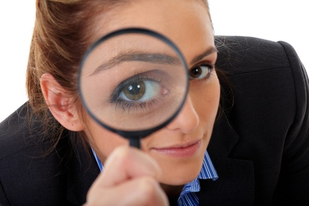 Attractive businesswoman holds magnifying glass, search or spy concept, isolated on white Stock Photo