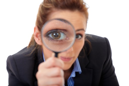 spy girl: Attractive businesswoman holds magnifying glass, search or spy concept, isolated on white Stock Photo