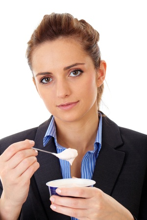Young attractive office girl eats yoghurt during her break, isolated on white photo