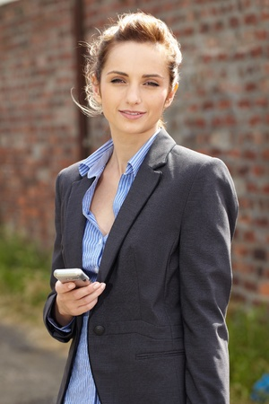 young businesswoman holds her mobile, outdoor shoot with blurred red brick wall as background, can be used as copy space photo