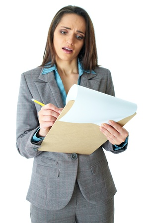 young attractive but shocked businesswoman makes some notes or calculation with pencil and paper on wooden board, isolated on white, foreground focus photo