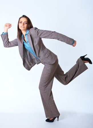 young happy businesswoman in a rush, run pose, isolated on white photo