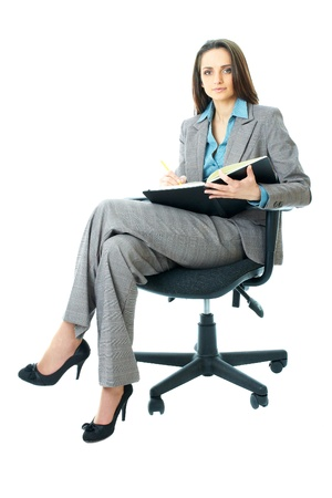 sits on a chair: young businesswoman sits on office chair and takes some notes, isolated on white