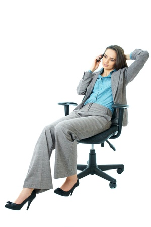 businesswoman in blue shirt and suit sits on office chair and talks over mobile phone, isolated on white photo