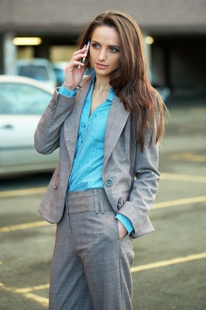 young very attractive female talks over her mobile phone, blurred car park as background, outdoor shoot Stock Photo - 11477835