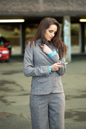 young attractive businesswoman trying to cover herself from chill, cold, while checks her mobile phone, car park as background Stock Photo - 11477794
