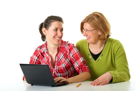 mother and her daughter working or surfing internet using small laptop, netbook, looking at each other, isolated on white