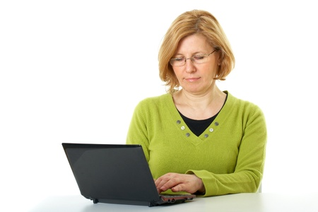 mujeres mayores: mujer madura en la parte superior verde y gafas trabaja en su netbook, aislado en blanco Foto de archivo