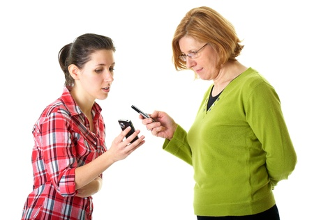 mother and daughter use their mobile phones, daughter shows something on her mobile, isolated on white