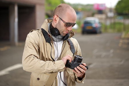 young photographer with his camera and headphones on his neck, outdoor shoot photo