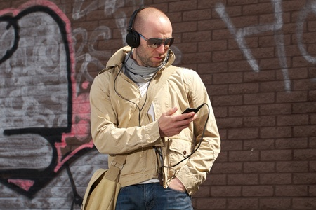 young male in khaki jacket listen to his music, wall with graffiti as background, outdoor shoot photo