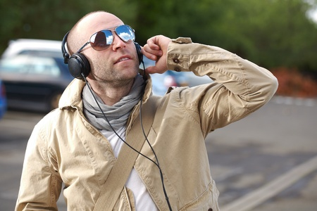 young male in khaki jacket listen to his music, outdoor shoot photo