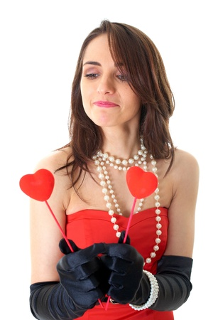 female in red dress holds two small red hearts in front of her, isolated on white background photo