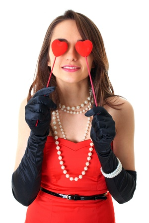 female in red dress holds two small red hearts in front of her eyes, love is blind concept, isolated on white photo