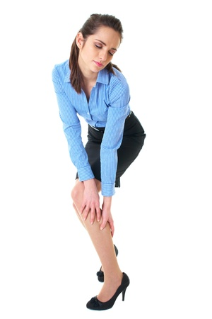 attractive brunette holds her calf, pain concept, wears blue shirt and pencil skirt, isolated on white