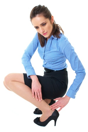pencil skirt: attractive brunette holds her calf, pain concept, wears blue shirt and pencil skirt, isolated on white