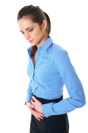 attractive brunette female suffers from stomachache, holds her hand on her belly, isolated on white