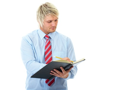young blonde businessman in blue shirt makes some notes in notepad, isolated on white photo