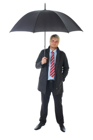 blonde businessman in blue shirt and dark coat holds black open umbrella over his head, isolated on white photo