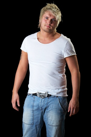 young attractive blonde male in white tshirt and jeans trousers isolated on black background