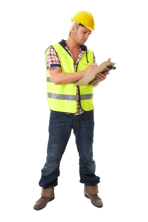 protective workwear: young blonde attractive builder, worker, wears yellow hardhat and hi-vis vest, takes some notes on his small board, isolated on white Stock Photo