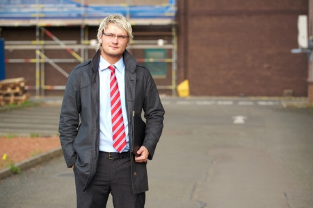 young blonde businessman with blurred office bulding as abckground photo