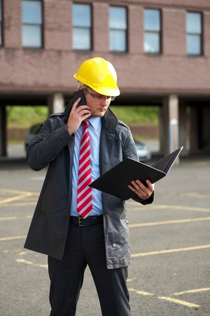 young architect or inspector with office building as blurred background, talks over his mobile phone photo