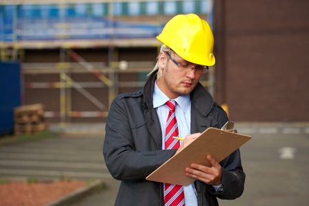 young architect or inspector make some notes, office buidling as background Stock Photo