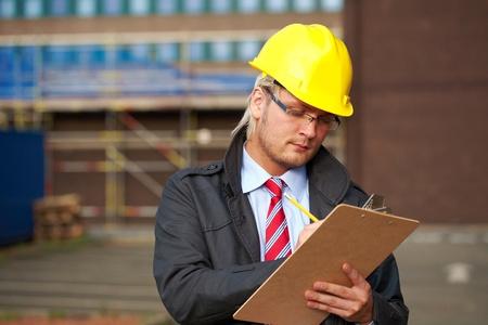 jonge architect of inspecteur te maken wat aantekeningen, kantoor gebouw als achtergrond wazig