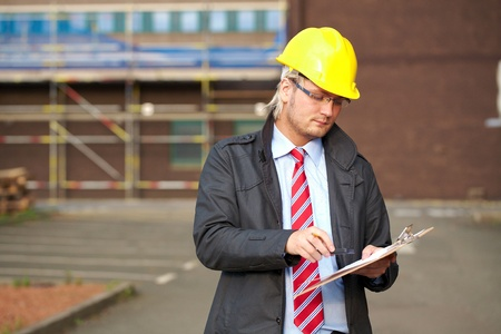 young architect or inspector with office building as blurred background photo