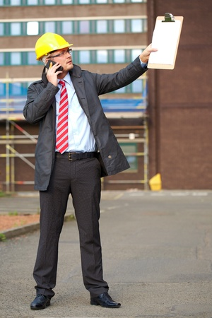 young architect, inspector talk over his mobile phone, outdoor shoot with blurred office building as background photo