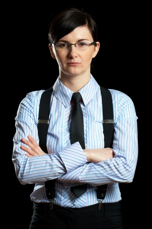 portrait of young businesswoman in shirt, braces and black tie, studio shoot isolated on black