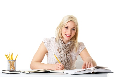 young attractive blonde female student makes some notes, isolated on white photo
