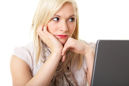 young distracted blonde office worker looks away from computer screen, isolated on white photo