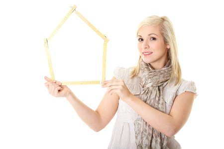 blonde young female holds house shaped measure tape, isolated on white photo