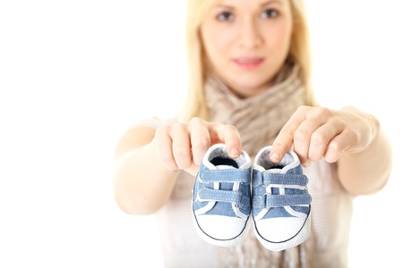 baby shoes: female holds little baby shoes, pregnancy concept, isolated on white