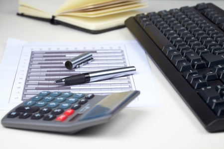 keyboard calculator and some paperwork on desk, graph with some financial data on it Stock Photo