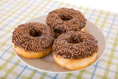 three chocolate donuts with sprinkles, placed on round plate and linen cloth in green and blue stripes photo