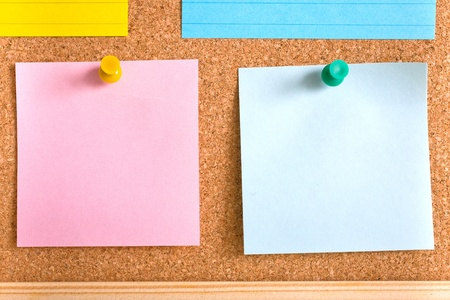 pink and blue sticky notes attached by yellow and green pins on cork board Stock Photo - 11617366